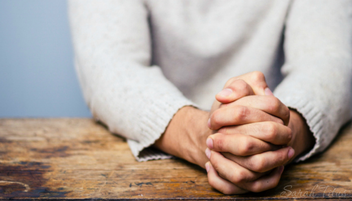 Person sitting at a desk praying