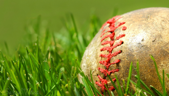 Worn baseball with red stitching laying in the grass