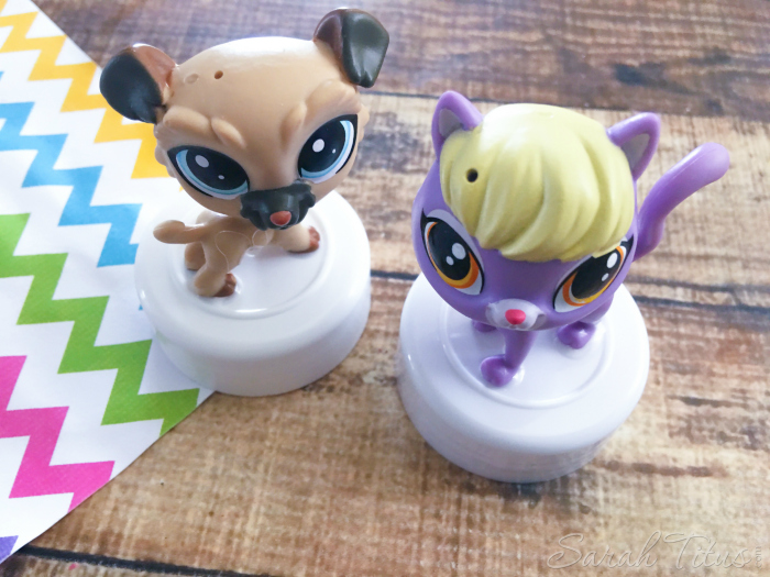 Littlest Pet Shop characters glued to small lids sitting on a wood table