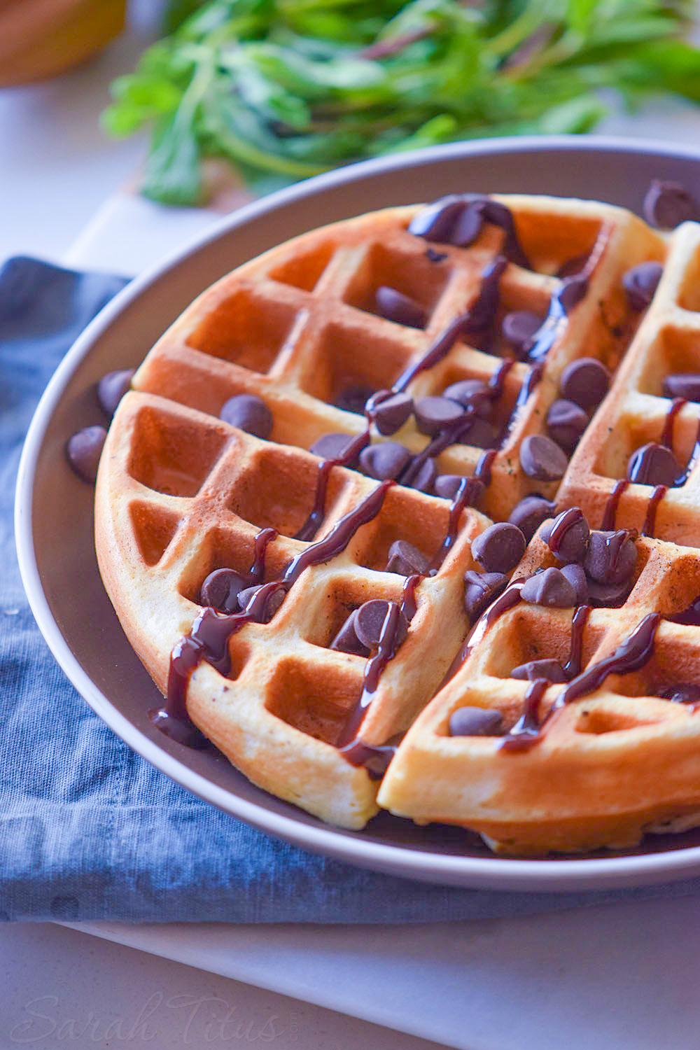Delicious looking crispy lightly browned waffle covered with drizzled chocolate and chocolate chips