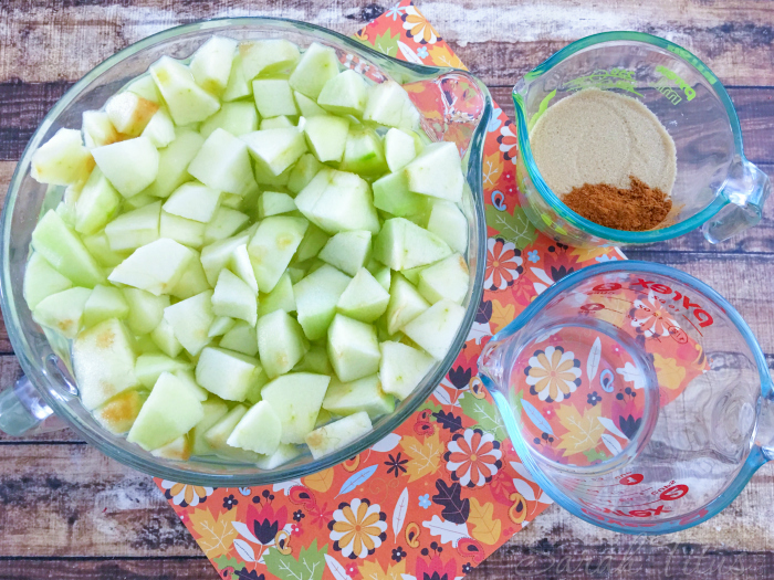 Sliced green apple in a glass measuring cup with cinnamon and sugar in another glass measuring cup and water in a glass measuring cup