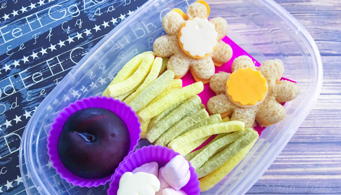 Flower Bento Box with a fresh plum, marshmallows, veggie straws and flower shaped turkey and cheese sandwiches