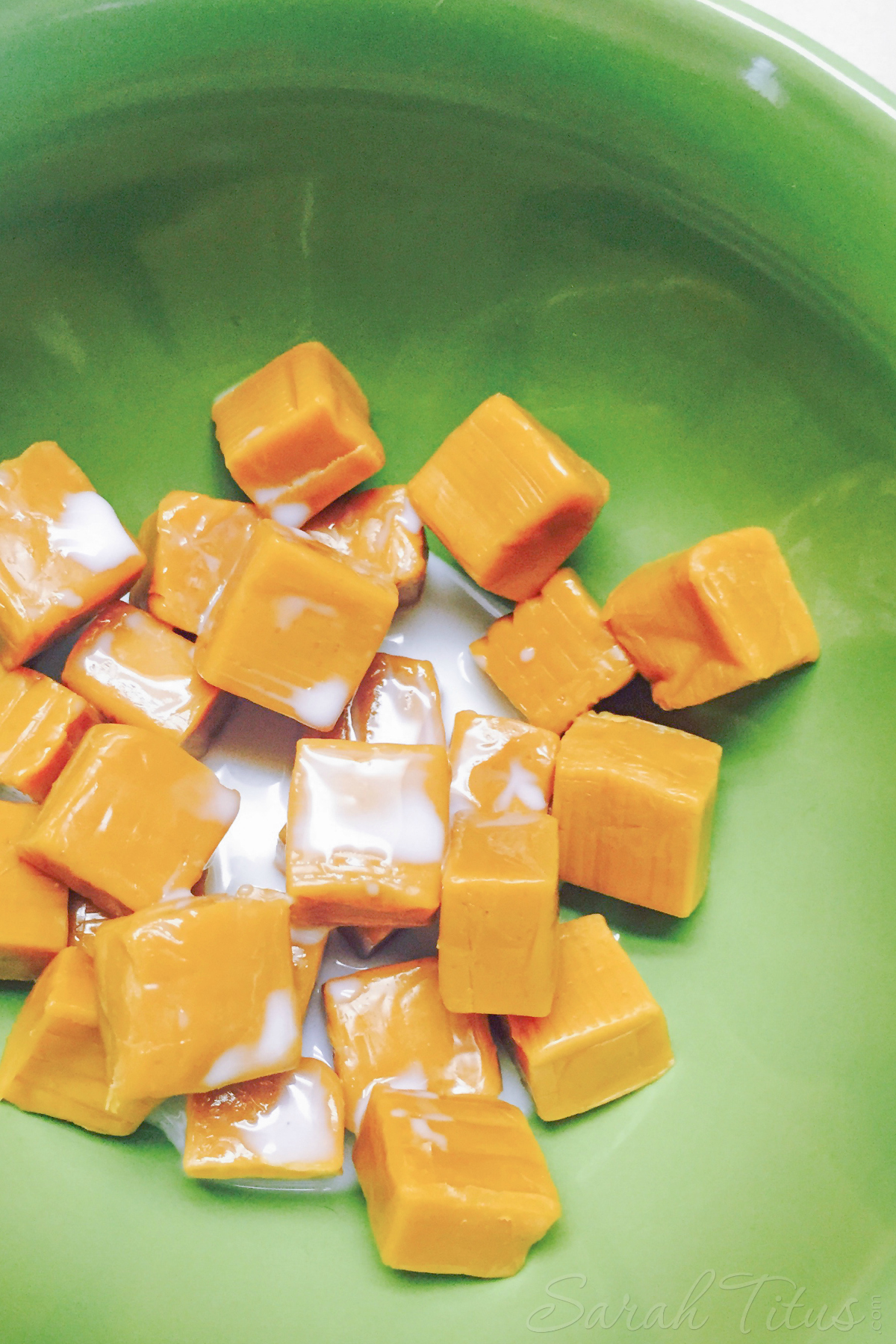 Caramels and milk in a green bowl