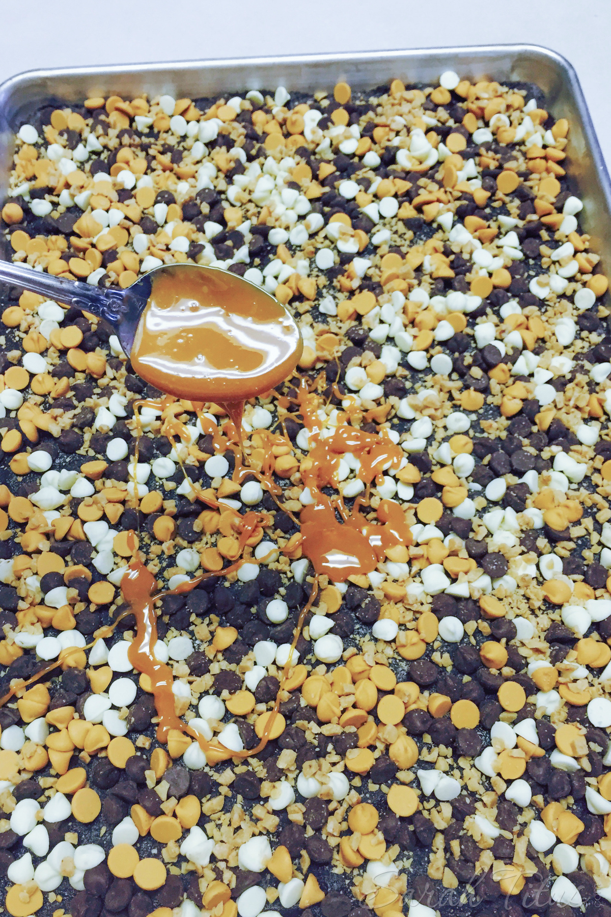 Drizzling melted caramel over the Salted Caramel Magic Bars in a silver baking dish