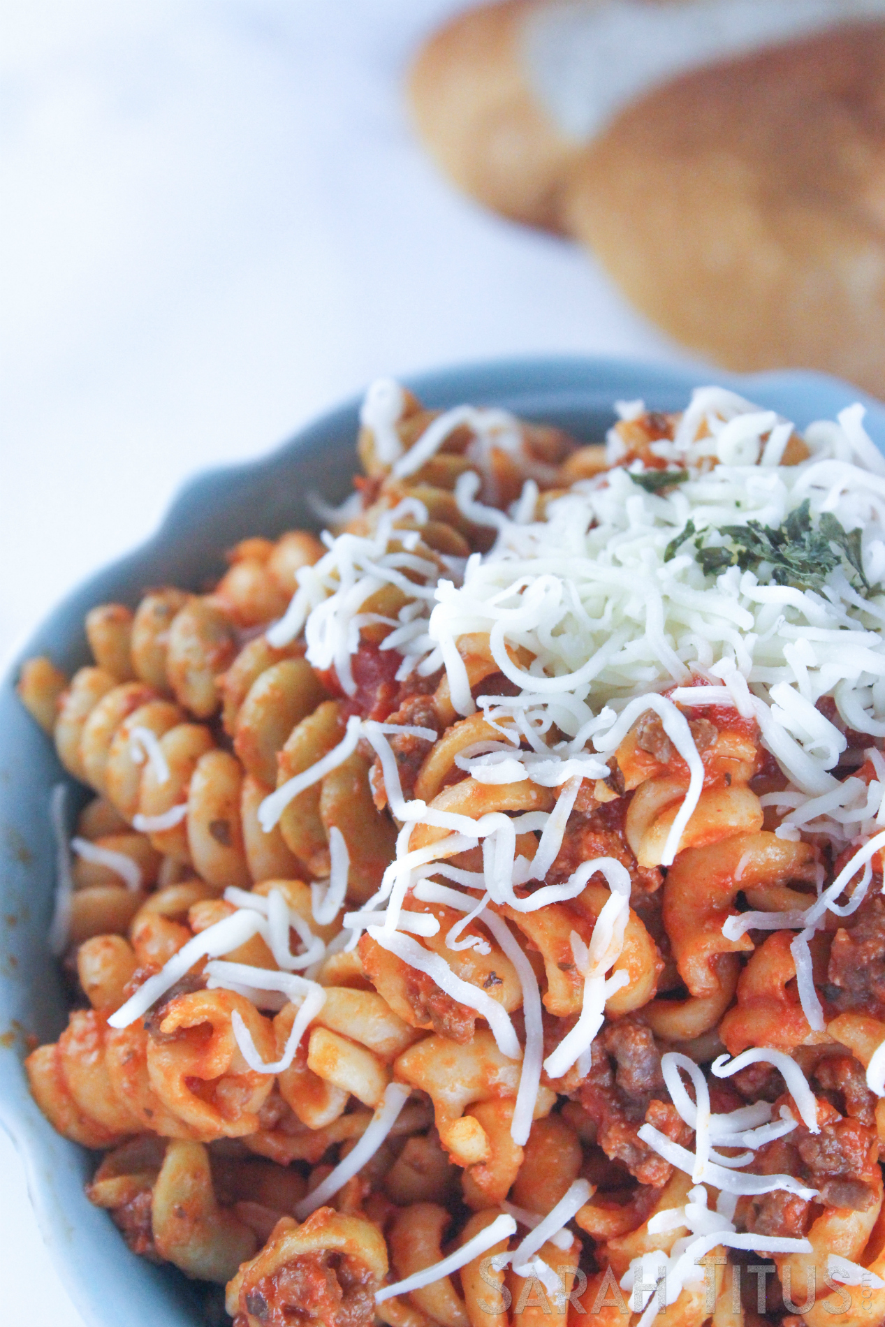 Spicy pasta with Parmesan cheese and a crusty loaf of bread