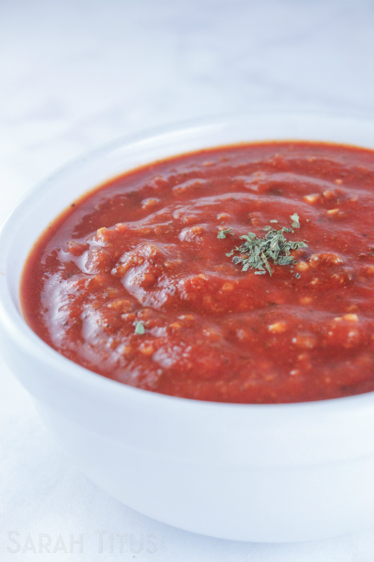 Luscious thick tomato sauce for pasta in a white bowl on a marble counter