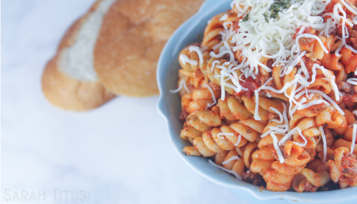 Spicy pasta with Parmesan cheese in a blue bowl with crusty bread