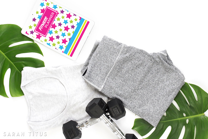 Preparing for exercise with clothing, weights and a fitness planner